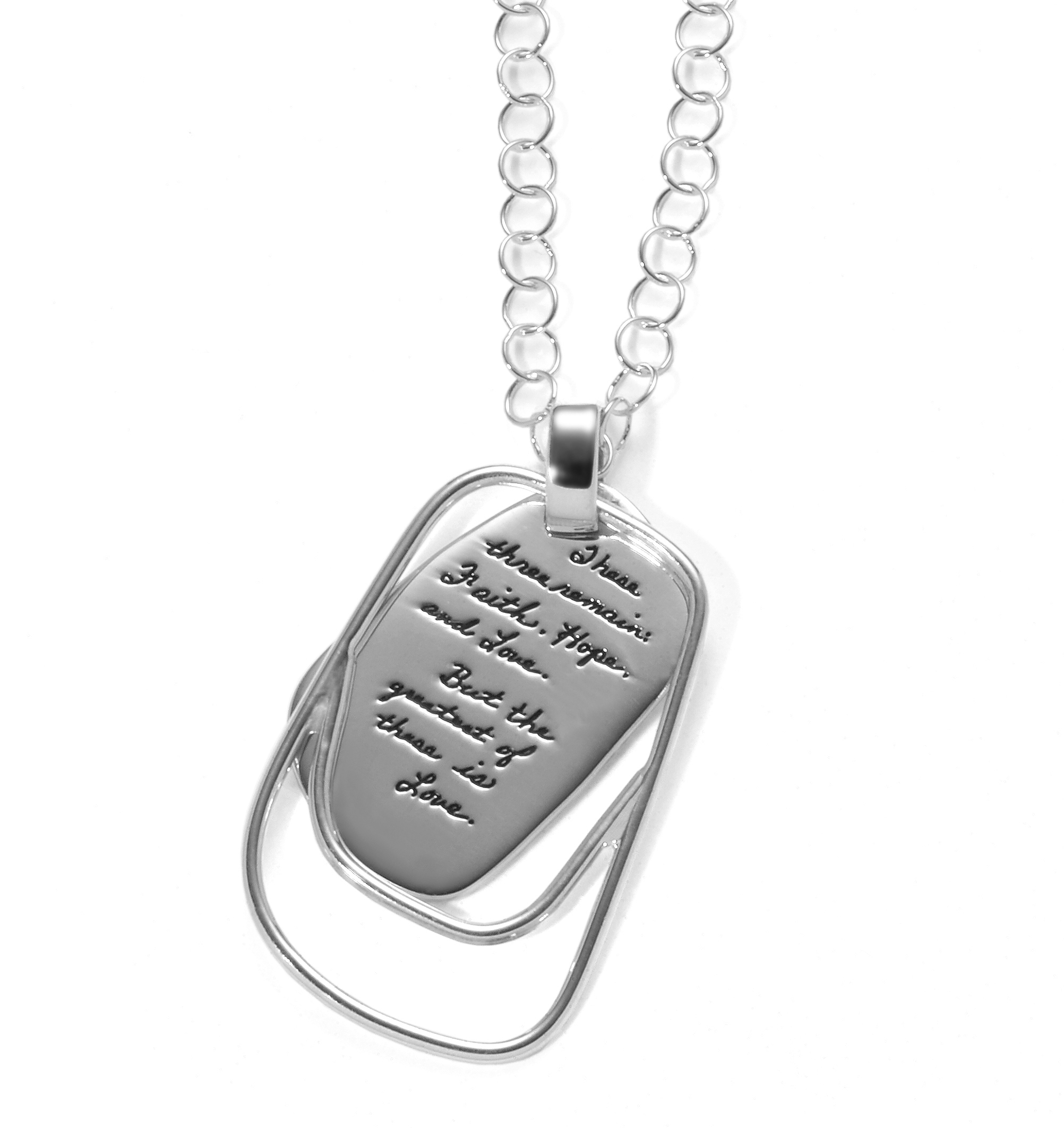 Sterling silver necklace in an irregular rectangle shape outlined with double sterling wire on the bottom. The engraved message reads: These three remain: Faith, Hope and Love. But the greatest of these is Love - 1st Corinthians