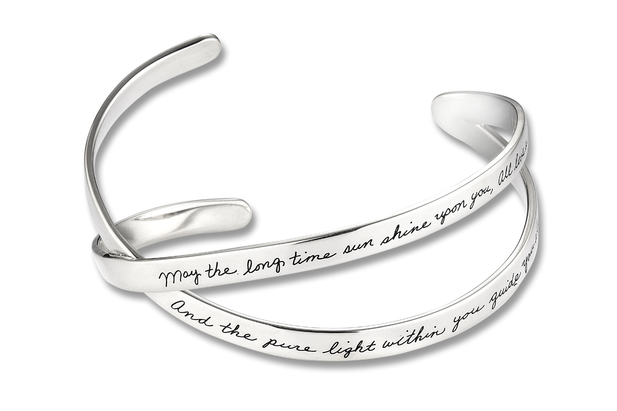 Bracelet with two silver bands crossing at mid point, merging at one end and open wide at other with engraved quote: May the Long Time Sun shine upon you, all love surround you, and the pure light within you  guide you all the way home.