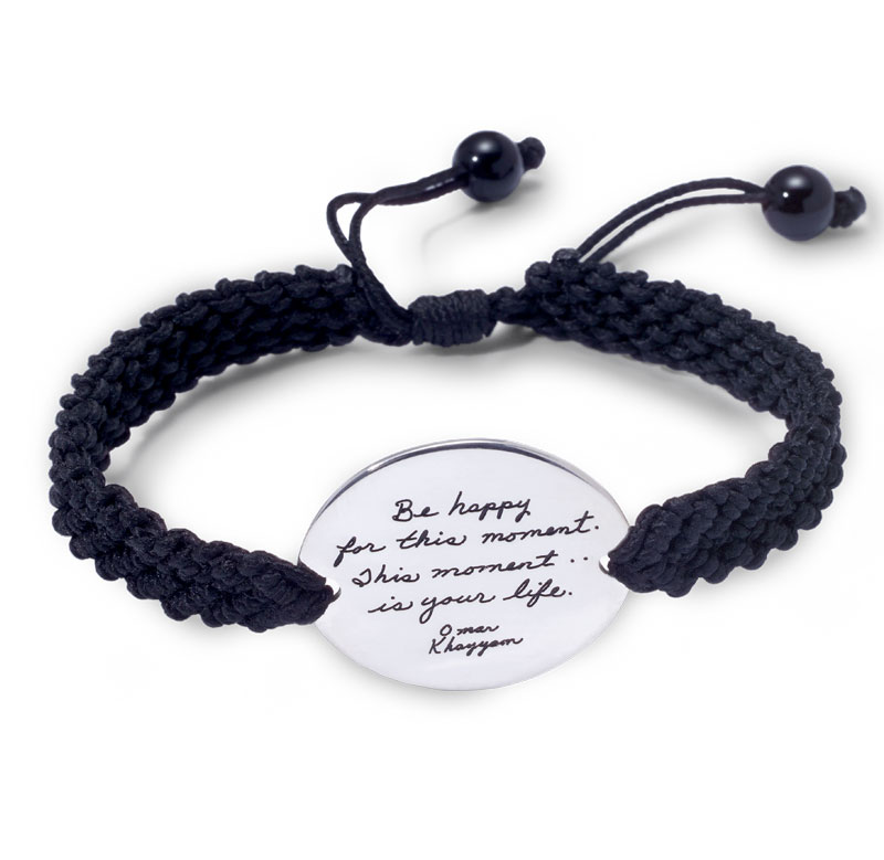 Silver bracelet with hand-woven black cord and sterling oval disc carries engraved words: Be happy for this moment. This moment is your life.