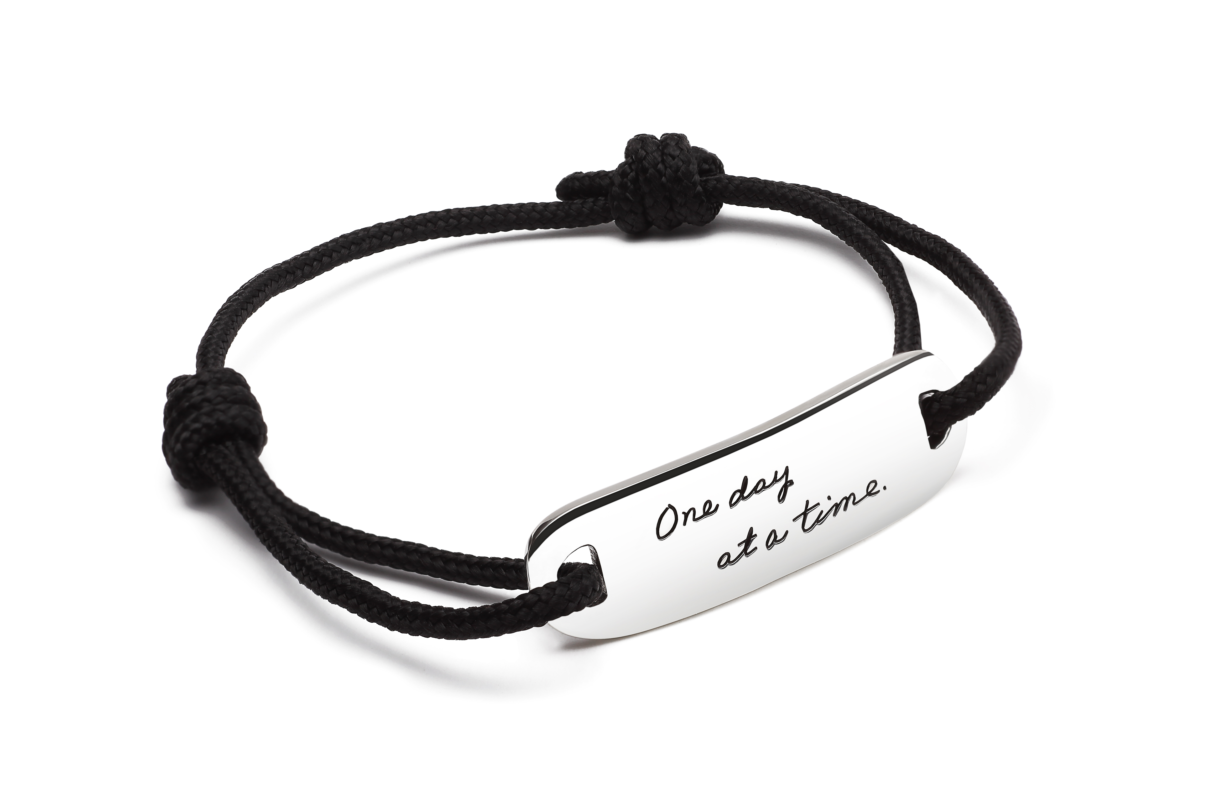 Black corded bracelet with Inspirational Sterling Silver horizonal long oval shape plaque with two half circle cutout on either end to attach cord quote reads: One day at a time.