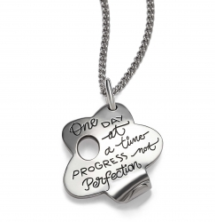 Inspirationa sterling silver quote necklace in the shape of a flower with the quote: One day at a time progress not perfection.